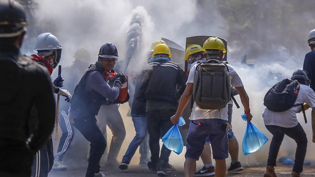 Anti-Putsch-Demonstranten setzen Feuerlöscher ein, um sich vor Tränengas zu schützen. Sicherheitskräfte in Myanmar haben in der Nacht zum Dienstag in Yangon rund zwei Dutzend Menschen festgenommen, nachdem sie zuvor viele Stunden lang Hunderte Demonstranten eingekesselt hatten. Foto: Str/AP/dpa