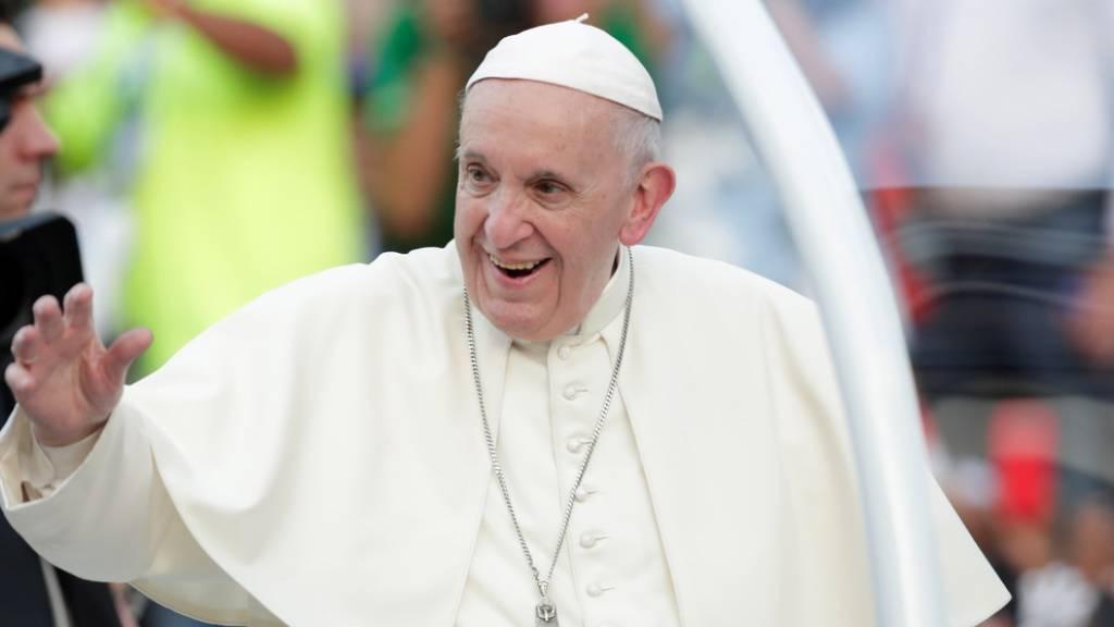 Papst Franziskus freut sich über eine geschenkte Krippe, in der Maria schläft, während sich Josef um das Kind kümmert.
