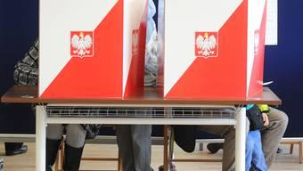 Wähler hinter Wahlurnen in der polnischen Hauptstadt Warschau. (Archivbild)