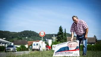 Werner Kalt, Landwirt in Kleindöttingen, stellt ein umgefallenes SVP-Plakat auf seinem Land wieder auf – dass die CVP bei ihm ungefragt Wahlplakate aufgestellt hat, ärgert ihn aber.