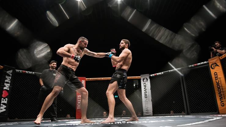Ein Blick durch das Käfiggitter: Noch stehen Mijo Milos (links) und David Moscateli, schon bald geht die Prügelei auf dem Boden weiter...