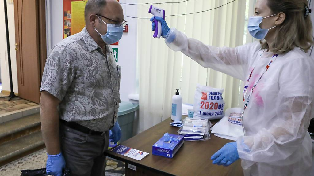 Eine medizinische Mitarbeiterin überprüft in Moskau überprüft die Körpertemperatur eines Mannes. Foto: Sofia Sandurskaya/AP/dpa