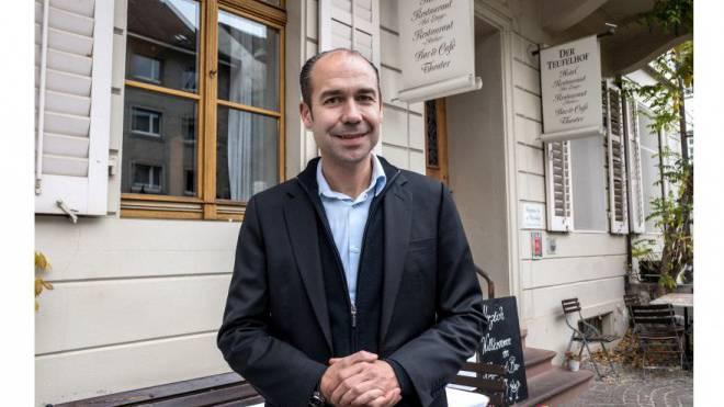 Raphael Wyniger vor dem Hotel Teufelhof. In dessen Fenstern spiegelt sich die Liegenschaft, die er zu einem Hotel umfunktionieren möchte. Foto: Kenneth Nars