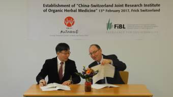 FiBL-Direktor Urs Niggli und Miao Jianhua, Direktor des Guangxi Botanical Garden of Medicinal Plants unterzeichnen den Vertrag für eine zehnjährige Zusammenarbeit.