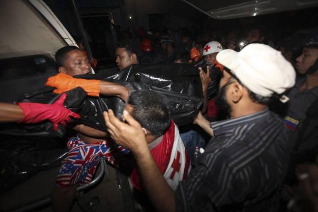 Mitglieder des Roten Kreuzes helfen bei der Bergung der Toten mit