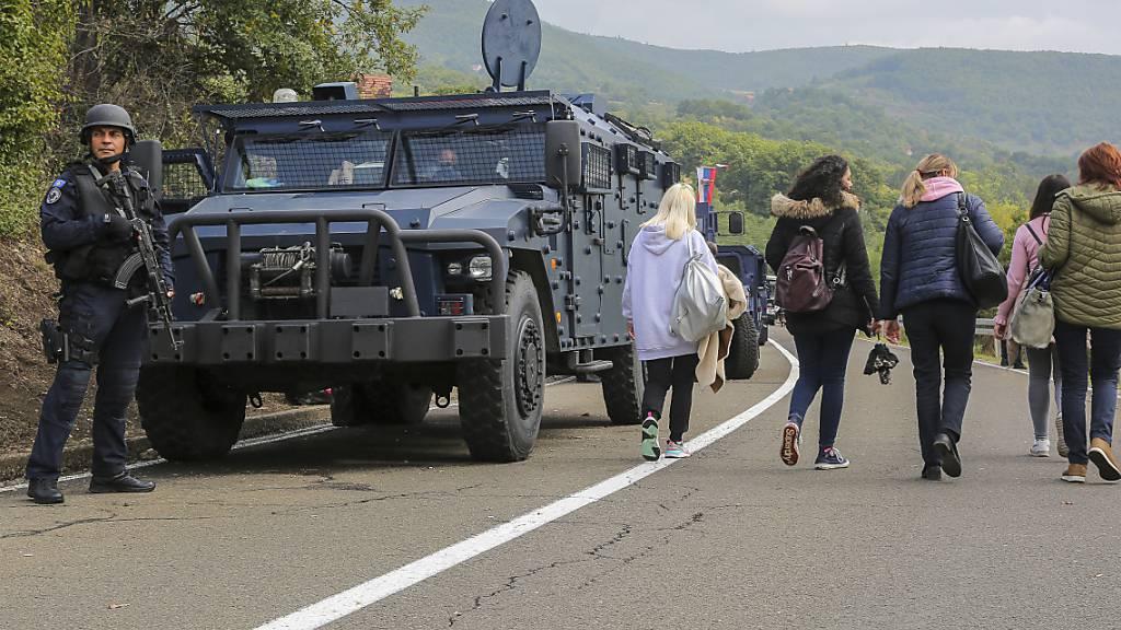 Ein kosovarischer Soldat hält eine Waffe in der Hand und steht auf einer Straße in der Nähe des Grenzortes Jarinje, während Personen an ihm vorbeigehen. Zwischen dem Kosovo und Serbien ist es wegen einer neuen Verordnung über die Zulässigkeit von Kfz-Kennzeichen zu Spannungen gekommen. Foto: Visar Kryeziu/AP/dpa