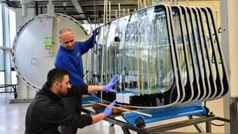 Glas-Trösch-Mitarbeiter Milot Gaxherri (links) und Dilaver Bekiri mit Frontscheiben für Rolls-Royce.