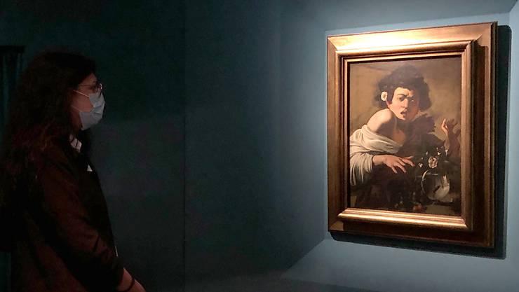 Ein Frau vor dem Gemälde «Jüngling, von einer Eidechse gebissen» von Michelangelo Merisi da Caravaggio in der Sonderausstellung in den Kapitolinischen Museen. Foto: Alvise Armellini/dpa - ACHTUNG: Nur zur redaktionellen Verwendung im Zusammenhang mit einer Berichterstattung über die Ausstellung und nur mit vollständiger Nennung des vorstehenden Credits