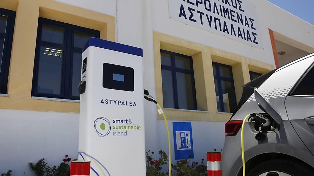 Ein Elektroauto wird auf dem Parkplatz des Flughafens auf der griechischen Insel Astypalea aufgeladen. Seit dem 2. Juni sind die Bewohner der Insel vollkommen elektrisch unterwegs.