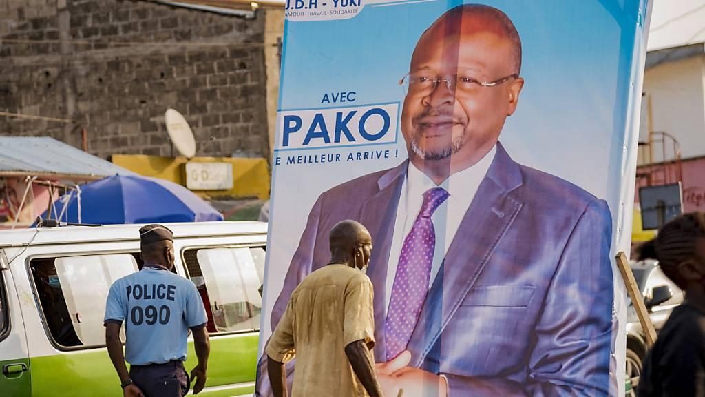 Menschen gehen an einem Wahlplakat des oppositionellen Präsidentschaftskandidaten Guy Brice Parfait Kolelas vorbei. Foto: Lebon Chansard Ziavoula/AP/dpa
