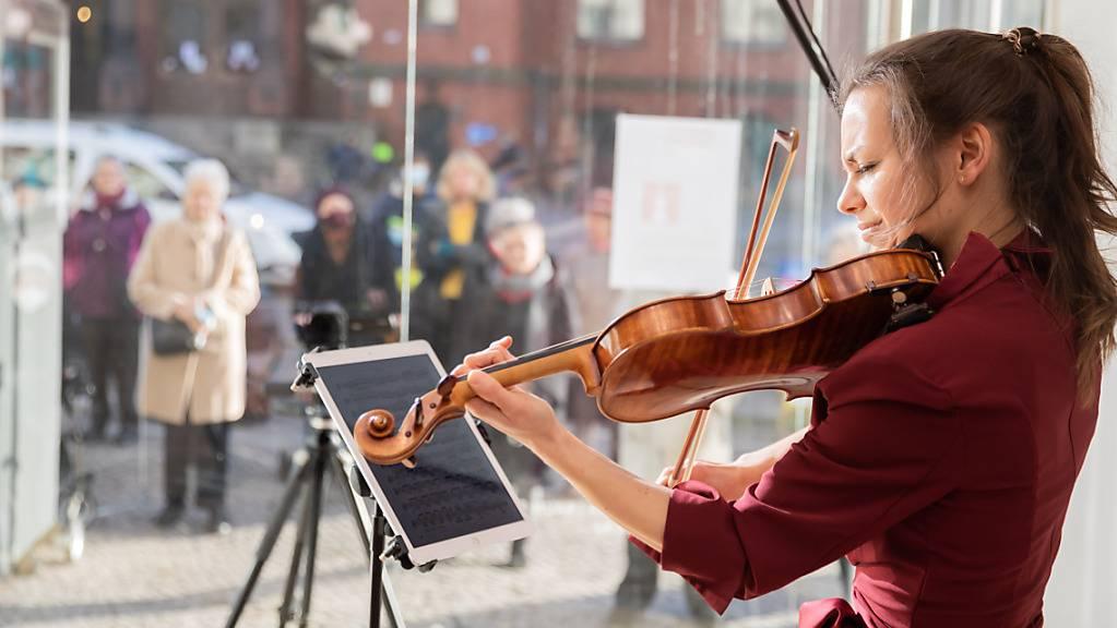dpatopbilder - Johanna Staemmler, Initiatorin der «Window Concerts», bei einem Auftritt im Schaufenster einer Berliner Galerie. Foto: Christoph Soeder/dpa