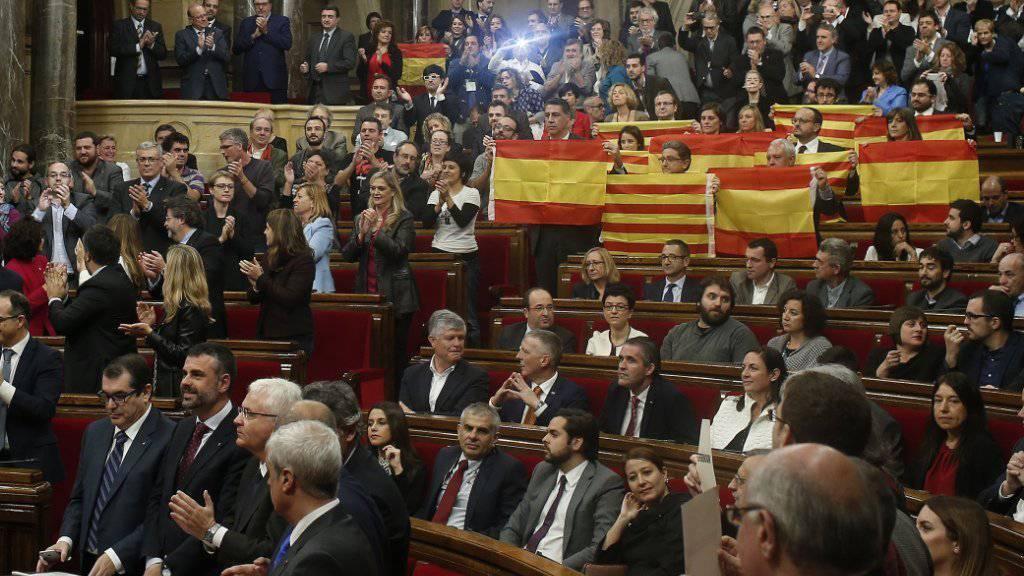 Mitglieder der Volkpartei PPC halten vor der Abstimmung im Parlament spanische und katalanische Flaggen in die Höhe - aus Protest gegen die bevorstehende Annahme der Abspalungsresolution.