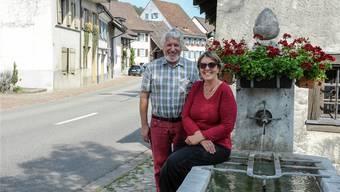 Paul Spiess (links) und Kathrin Stohler – sie führen seit März gemeinsam den Verein für Heimatpflege Ziefen – am Dorfbrunnen vor dem Bachhüsli.