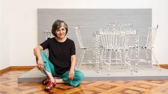 Die international bekannte Künstlerin Carmen Perrin vor ihrer Installation «Chicas!». Ein Tisch und fünf Stühle, die fast aus unserer Wahrnehmung verschwinden. bar