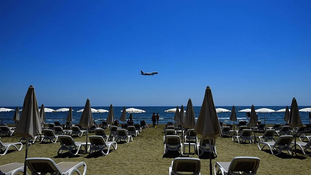 ARCHIV - Einige Menschen sonnen sich am Makenzi Strand während sich im Hintergrund ein Flugzeug auf die Landung am internationalen Flughafen Larnaca vorbereitet. Foto: Petros Karadjias/AP/dpa