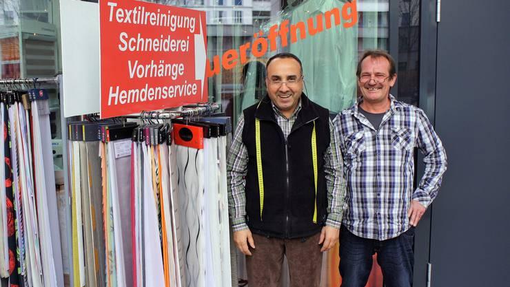 Vorhanghändler Ali Kömürcü und Schuhreparateur Alexander Kupfer planen, zusammen ein Werbeplakat für ihre Geschäfte aufzuhängen.
