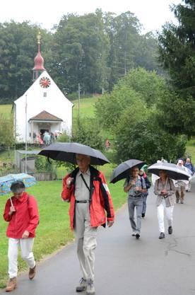 Die Kapellenwanderer im Regen unterwegs von der Laurentiuskapelle Wallenschwil (Hintergrund) nach Beinwil.