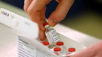 Ein Fläschchen des neu zugelassenen Impfstoffs gegen das Coronavirus der Universität Oxford und dem Pharmakonzern Astrazeneca wird aus einer Schachtel genommen, nachdem die erste Lieferung im Princess Royal Hospital eingetroffen ist. Foto: Gareth Fuller/PA Wire/dpa