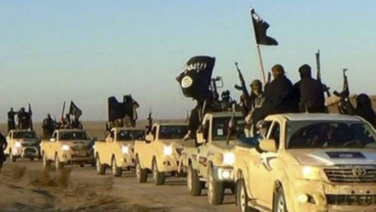 """Ein Konvoi von Kämpfern der Terrormiliz Islamischer Staat auf dem Weg von ihrer damaligen """"Hauptstadt"""" Rakka in Syrien in den Irak (2014 – Bild: KEYSTONE/AP/UNCREDITED)."""