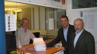 Baueingabe in Eiken: Häring-CEO Oscar Elias (Mitte) und Chefplaner Mario Cerri (rechts) mit dem Eiker Gemeindeschreiber Marcel Weiss.  pd