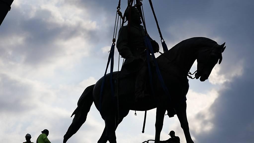 Arbeiter entfernen eine Bronzefigur des Südstaaten-Generals Robert Edward Lee. Robert E. Lee führte die Konföderierten im Bürgerkrieg der Südstaaten gegen die Nordstaaten. Lee wird von der rechten Szene in den USA als Held verklärt. Foto: Steve Helber/AP POOL/dpa