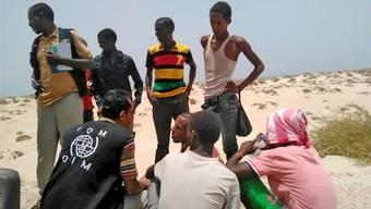 Ein Mitarbeiter der Internationalen Organisation für Migration spricht mit geretteten Flüchtlingen. keystone