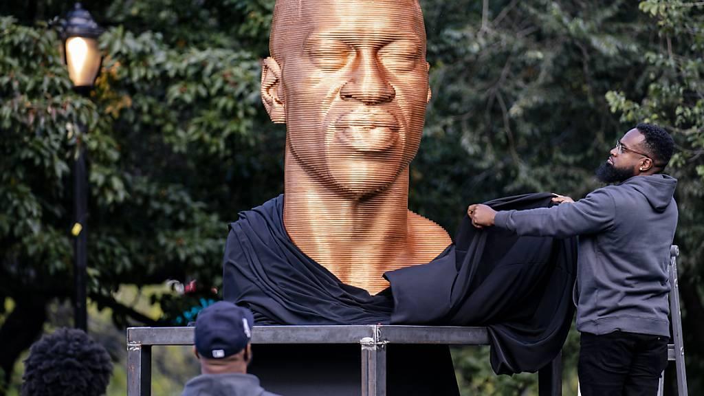 ARCHIV - Die Skulptur von George Floyd wird enthüllt. Sie ist in New York verunstaltet worden. Ein Mann auf einem Skateboard war am Sonntag (Ortszeit) auf die Statue zugefahren, beschmierte sie mit Farbe und flüchtete, wie US-Medien unter Berufung auf die Polizei berichteten. Foto: John Minchillo/AP/dpa