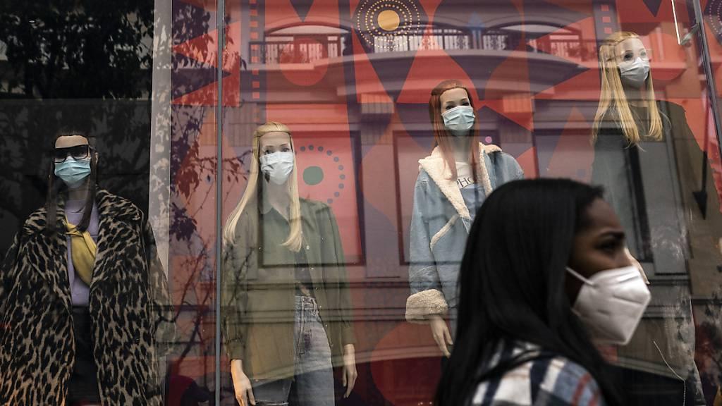 Eine Käuferin geht in Los Angeles an Schaufensterpuppen mit Mund-Nasen-Schutz vorbei. Große Teile Südkaliforniens befinden sich ab Montag, den 07.12.2020 im Lockdown, um die ansteigende Zahl der Corona-Fälle und Krankenhauseinweisungen zu verringern. Foto: Jae C. Hong/AP/dpa
