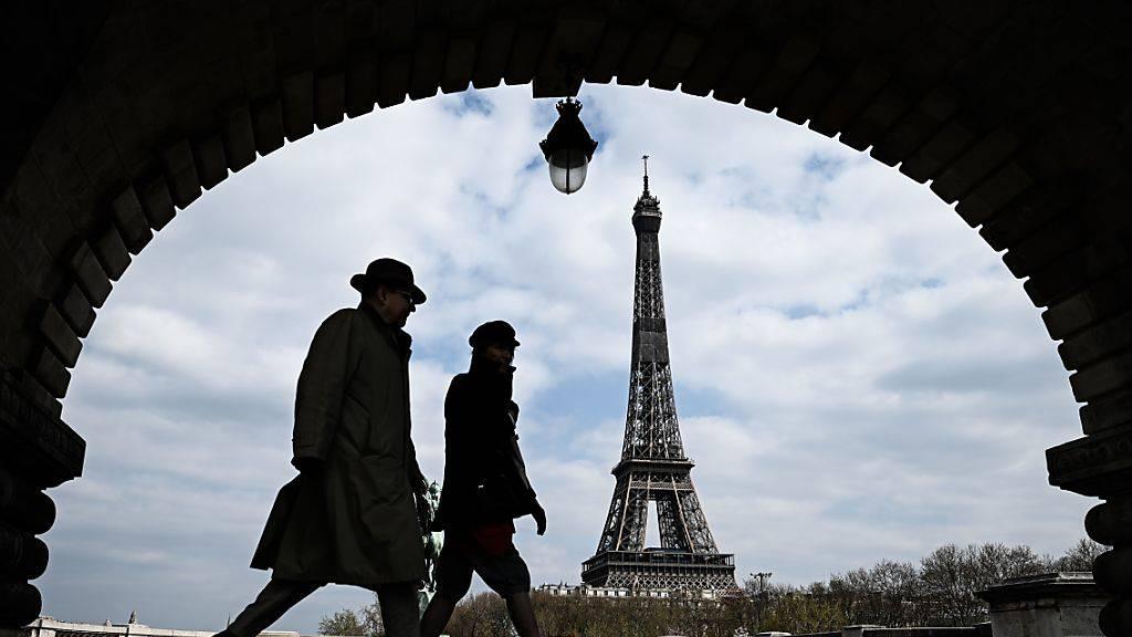 ARCHIV - Passanten gehen auf der Brücke «Pont de Bir-Hakeim», mit Blick auf den Eiffelturm. Foto: Philippe Lopez/AFP/dpa