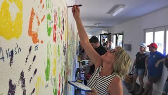 Besucherinnen und Besucher haben sich malerisch im Eingangsbereich verewigt. Im Bild Künstlerin Ute Cavelti.