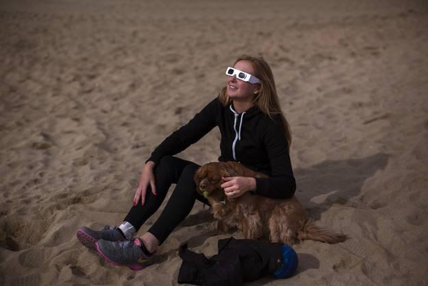 Eine Engländerin beobachtet die Sonnenfinsternis vom Strand in Barcelona, Spanien.