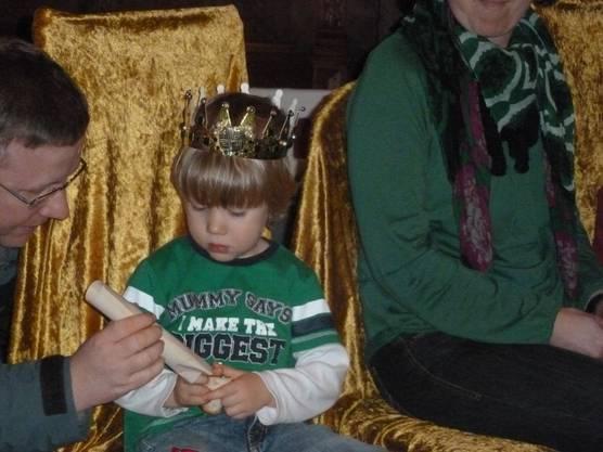 Der dreijährige König Tim Köhler übergibt seine Königsurkunde seinem Vater