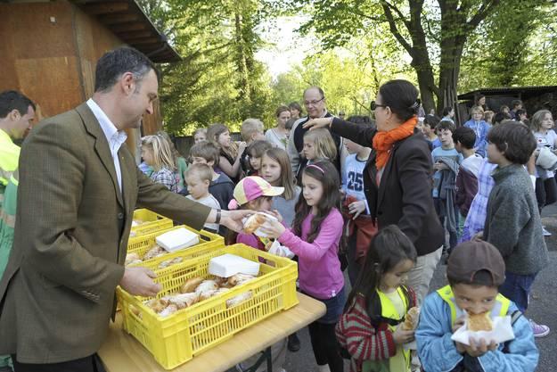 Emanuel Trueb von der Stadtgärtnerei verteilt an die fleissigen Helfer Weggli in Lärchenzapfenform.
