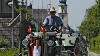 Arthur Berger (1950), mit Traktor Hürlimann D100, Jahrgang 1947, unterwegs im Unterdorf von Kestenholz Bild 442 Arthur Berger mäht eine Wiese mit einem Hürlimann D100, ausgerüstet mit dem originalen Messerbalken sowie einem Graszetter. Bild 606 Unterwegs im Unterdorf von Kestenholz. Bild 816 Arthur Berger auf seinem Lanz Bulldog. Bild 852 Generationentreffen: Der Lanz Bulldog wird mit einem topmodernen Rigi-Trac auf den Tieflader geschoben. Bild 902 Bereit für den Transport auf dem Tieflader (v.l.): Lanz Bulldog Mops, Hürlimann D200 Militär, Hürlimann D100 mit Pflug.