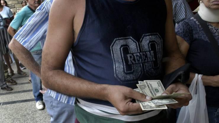 Ein Mann mit US-Dollars vor einer Wechselstube in der kubanischen Hauptstadt Havanna. (Archivbild)