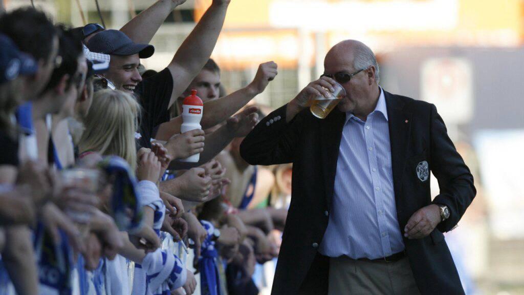 FCL-Präsident Walter Stierli bewacht am Match zwischen Luzern und Lugano 2009 die Fans und erhält von diesen ein Bier spendiert. (Archivaufnahme)