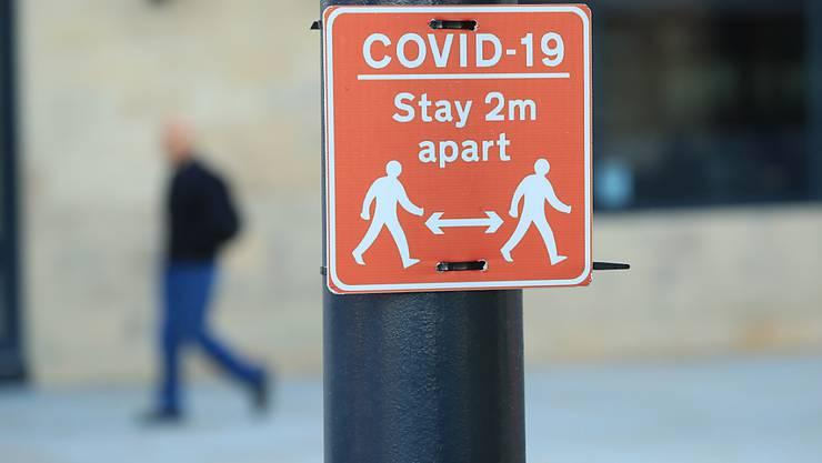 Ein Schild, das eine der Corona-Regeln abbildet, erinnert an die Einhaltung eines Mindestabstands von zwei Metern und ist an einer Laterne fixiert. Foto: Danny Lawson/PA Wire/dpa