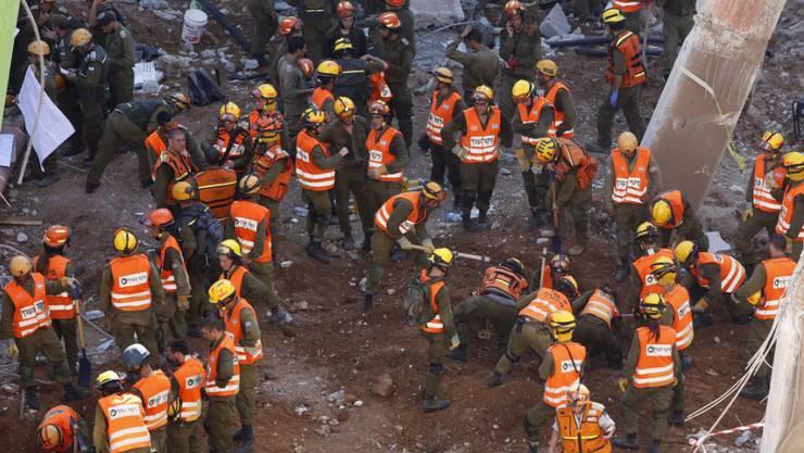 Helfer suchen unter den Trümmern nach verschütteten Personen.