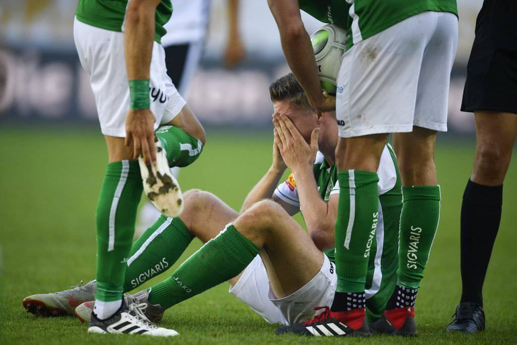 St.Gallens Cedric Itten sitzt während des Spiels gegen den FC Lugano verletzt am Boden.