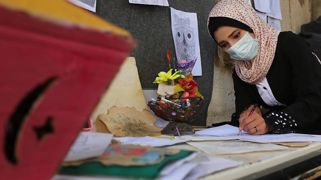 Die palästinensische Künstlerin Asma al-Aqra'a zeichnet Wahlurnen auf Papier in ihrem Haus vor den palästinensischen Parlamentswahlen. Foto: Ashraf Amra/APA Images via ZUMA Wire/dpa