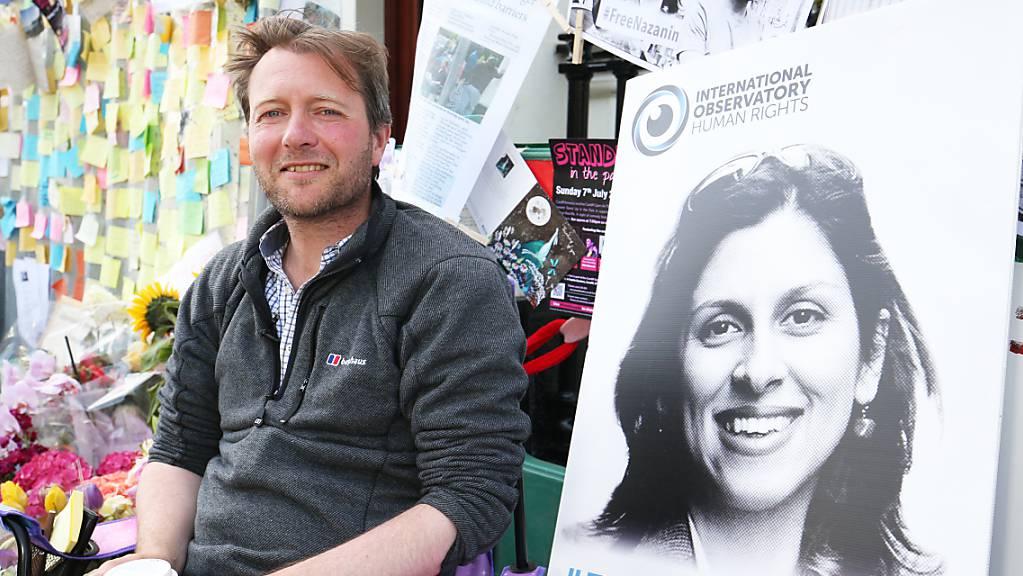 Richard Ratcliffe, der Ehemann der im Iran inhaftierten Nazanin Zaghari-Ratcliffe, sitzt neben einem Bild seiner Frau vor der iranischen Botschaft in London. (Archiv)