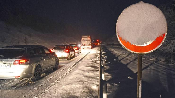 Autos und Lkw stehen am Freitagmorgen in der Nähe von Blankenheim (Nordrhein-Westfalen) am Ende der Autobahn A1 Richtung Süden. Nach den starken Schneefaellen am frühen Morgen ist der Verkehrsfluss in den Höhen der Eifel gestört.