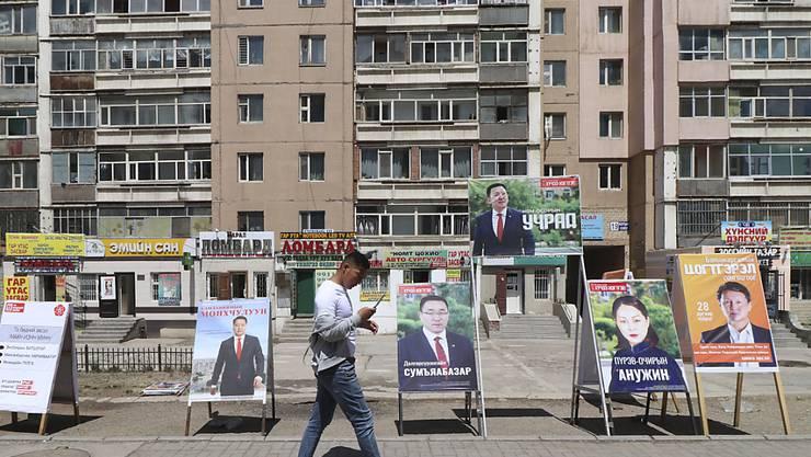 Ein Mann geht an Wahlplakaten verschiedener Parteien vorbei. Foto: Ganbat Namjilsangarav/AP/dpa