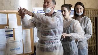 dpatopbilder - Mitglieder der Wahlkommission, die Schutzkleidung tragen, bereiten sich vor der Eröffnung eines Wahllokals vor. Noch bis Mittwoch, 01. Juli, können die Menschen über eine Verfassungsänderung abstimmen, die Präsident Putin dauerhaft die Macht sichern soll. Foto: Alexander Zemlianichenko/AP/dpa