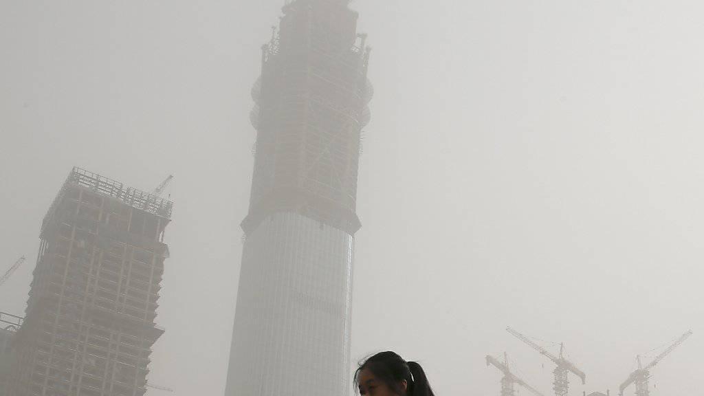 In Nordchina haben Sandstürme die Schadstoffwerte in der Luft in die Höhe schnellen lassen. Eine Frau in der Hauptstadt Peking, wo am Donnerstag der empfohlene Grenzwert für Feinstaub das 25-fache überstiegen hat, hält sich deswegen die Hand vor den Mund.