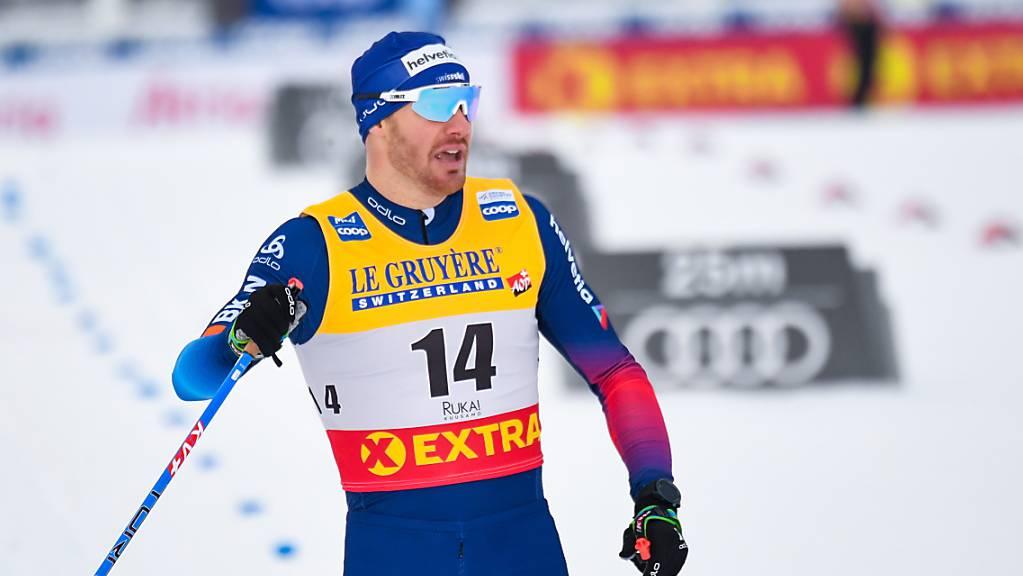 Dario Cologna mit Blick auf die Uhr beim Zieleinlauf.