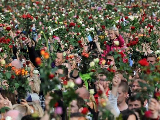 Tausende Menschen in Oslo gedenken mit einer Rose in den Händen der Opfer des Doppelanschlages