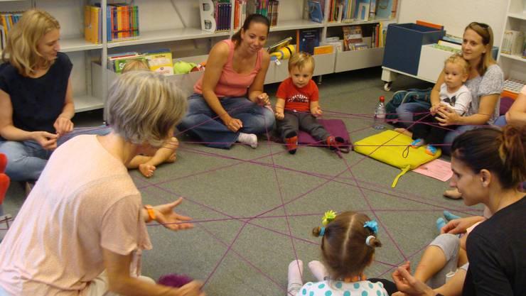 """Die Kinder und Mütter verdeutlichen die Geschichte """"Die kleine Spinne spinnt und schweigt"""" mit einem Spinnennetz aus Faden."""
