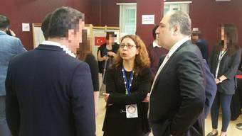 AKP-Mann Mustafa Yeneroglu im Gespräch mit der türkischen Generalkonsulin in Zürich. Im Hintergrund die Wahlkabinen für die Stimmabgabe zur Verfassungsreform.