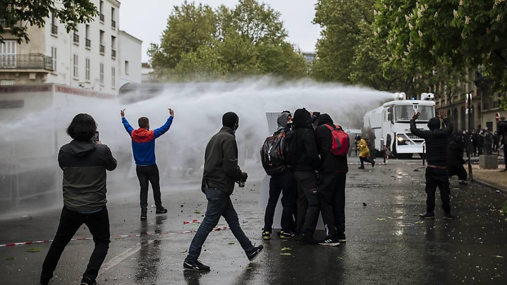 Polizisten setzen einen Wasserwerfer gegen Demonstranten auf dem Place de la Nation ein. Foto: Lewis Joly/AP/dpa